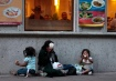 A homeless woman and her children sit outside a restaurant as she waits to receive a handout in Mexico City's historic Zocalo Square December 10, 2008. Picture taken on Dec 10. REUTERS/Henry Romero(MEXICO)
