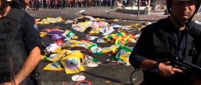 Cuerpos de víctimas cubiertos por banderas y pancartas, mientras agentes de policías aseguran la zona tras una explosión en Ankara, Turquía, el sábado 10 de octubre de 2015. Dos bombas estallaron con unos minutos de diferencia cerca de la estación de tren de Ankara antes de la marcha, organizada por el sindicato de trabajadores del sector público turco. La protesta pretendía pedir el fin de la renovada violencia entre rebeldes curdos y fuerzas de seguridad turcas.. (AP Foto/Burhan Ozbilici)