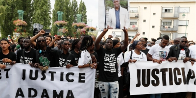 "People hold a portrait picture of Adama Traore and a banner reading ""Truth and justice for Adama"" as they attend a white march organised in tribute to the 24-year old man in Beaumont-sur-Oise on July 22, 2016. Violence erupted in the northern suburbs of Paris for a third night in a row on July 21, 2016, with 15 cars set ablaze by residents furious over the death of a young man in police custody. The unrest began on July 19 after it emerged that Adama Traore, 24, had died shortly after being arrested in the town of Beaumont-sur-Oise. Authorities said an autopsy revealed he was suffering from a serious infection at the time of his death and that his body showed few signs of violence. / AFP PHOTO / Thomas SAMSON"