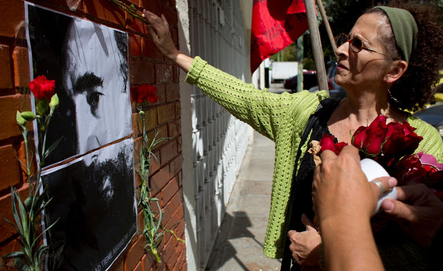 A woman places flowers on an image of Fidel Castro outside Cuba's embassy in Guatemala City, Saturday, Nov. 26, 2016