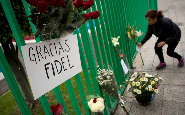 A woman leaves flowers and a handwritten note outside the Cuban embassy in Mexico City, Saturday, Nov. 26, 2016