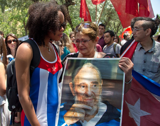 Women cry as they hold a poster of Cuba's historic revolutionary leader Fidel Castro outside the Cuban embassy in Santiago on November 26, 2016, the day after he died aged 90.