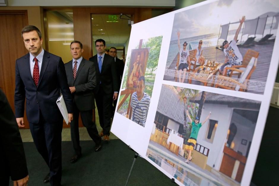 Trevor McFadden, a la izquierda, adjunto en funciones del asesor del fiscal general de EE UU, pasa junto con otros cargos ante una serie de fotografías del hacker ruso Román Selezniov.